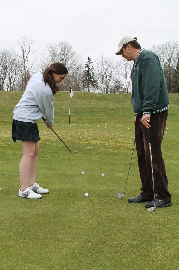 Assistant+golf+coach+Jim+Alfredo+works+with+sophomore+Emily+Kasper+on+her+chipping.%0AJane+Gerstner+%27+14