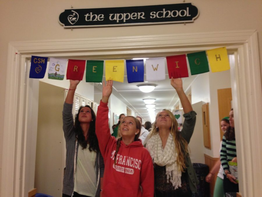 Sophomores+Corina+Gonzalez%2C+Riley+Doyle+and+Lilly+Morriss+reach+to+touch+the+flags+and+say+a+prayer+as+they+walk+through+the+Upper+School+hallway.%0ACourtesy+of+Mrs.+Lori+Wilson+