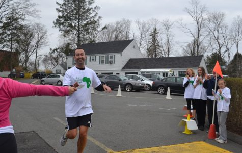 First place winner, Dr. Kevin Donnelly at the finish line of Run for Uganda after completing his 5K run for the benefit of the Sacred Heart secondary sister school in Uganda, Africa. courtesy of Mrs. Wilson