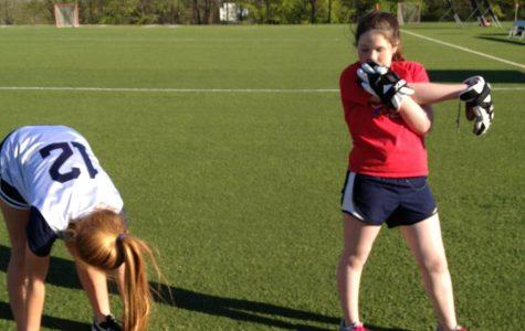 Freshmen Lucy Alderson-Smith and Elizabeth Considine stretch before lacrosse practice. courtesy of Maddie Caponiti '15