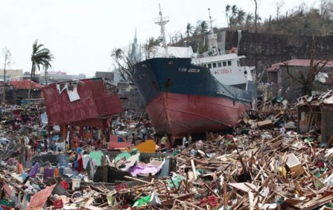 Survivors of the typhoon search for supplies amongst a ship washed ashore in Tacloban City, Leyte, located in the Philippines. Courtesy of thegaurdian.com