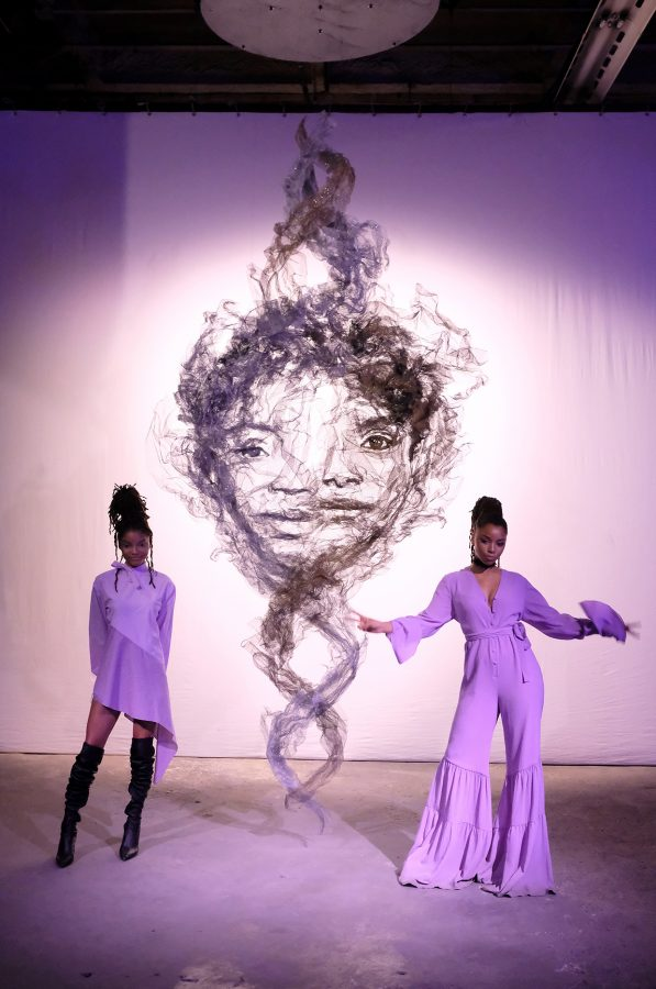 Chloe Bailey and Halle Bailey posing in front of their art installment. Courtesy of Nicholas Hunt/ Getty images for Refinery29 via Billboard.