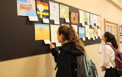 Students admiring Upper School artwork that was produced for the art exchange Anissa Arakal '19