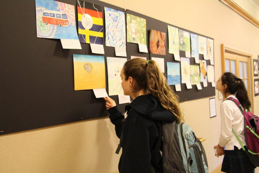 Students admiring Upper School artwork that was produced for the art exchange Anissa Arakal '19