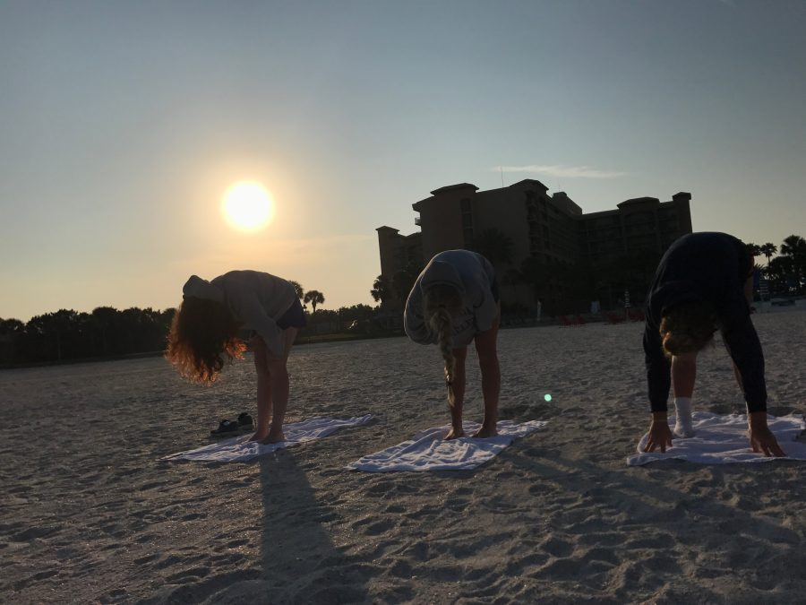 Varsity lacrosse team members participating in a beach yoga session.  Courtesy of Christina Deconcini '18