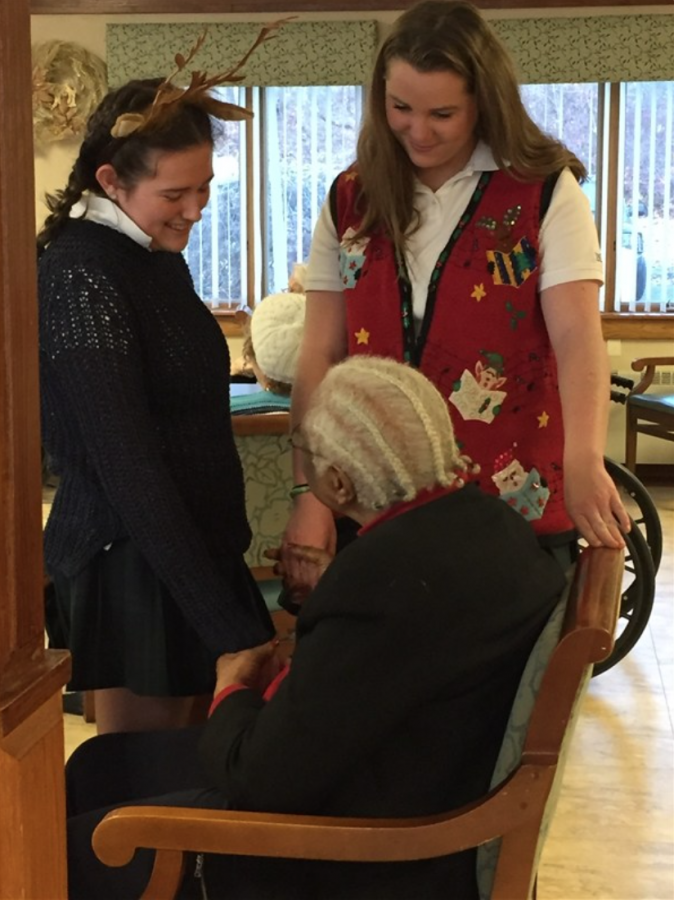 Seniors Hanna Sheehan 17 and Helen Rail 17 converse with residents. Courtesy of Delia Hughes 17.