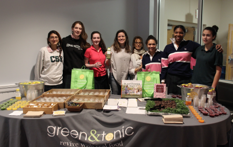 Ms. Patty Blank and Ms. Kristina Hess stand behind their Green and Tonic display with Sacred Heart seniors. Cheyann Greirson '16