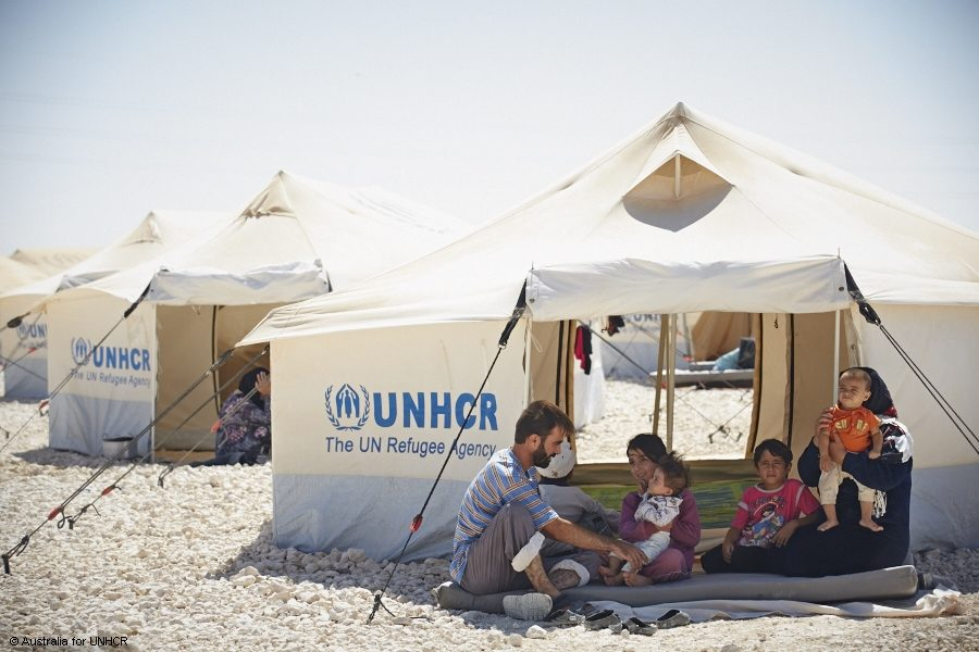 A Syrian refugee family gathers in front of their tent in a UNCHR refugee camp. Courtesy of unrefugees.org