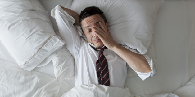 A business man struggling to balance sleep and work. Courtesy of huffingtonpost.com